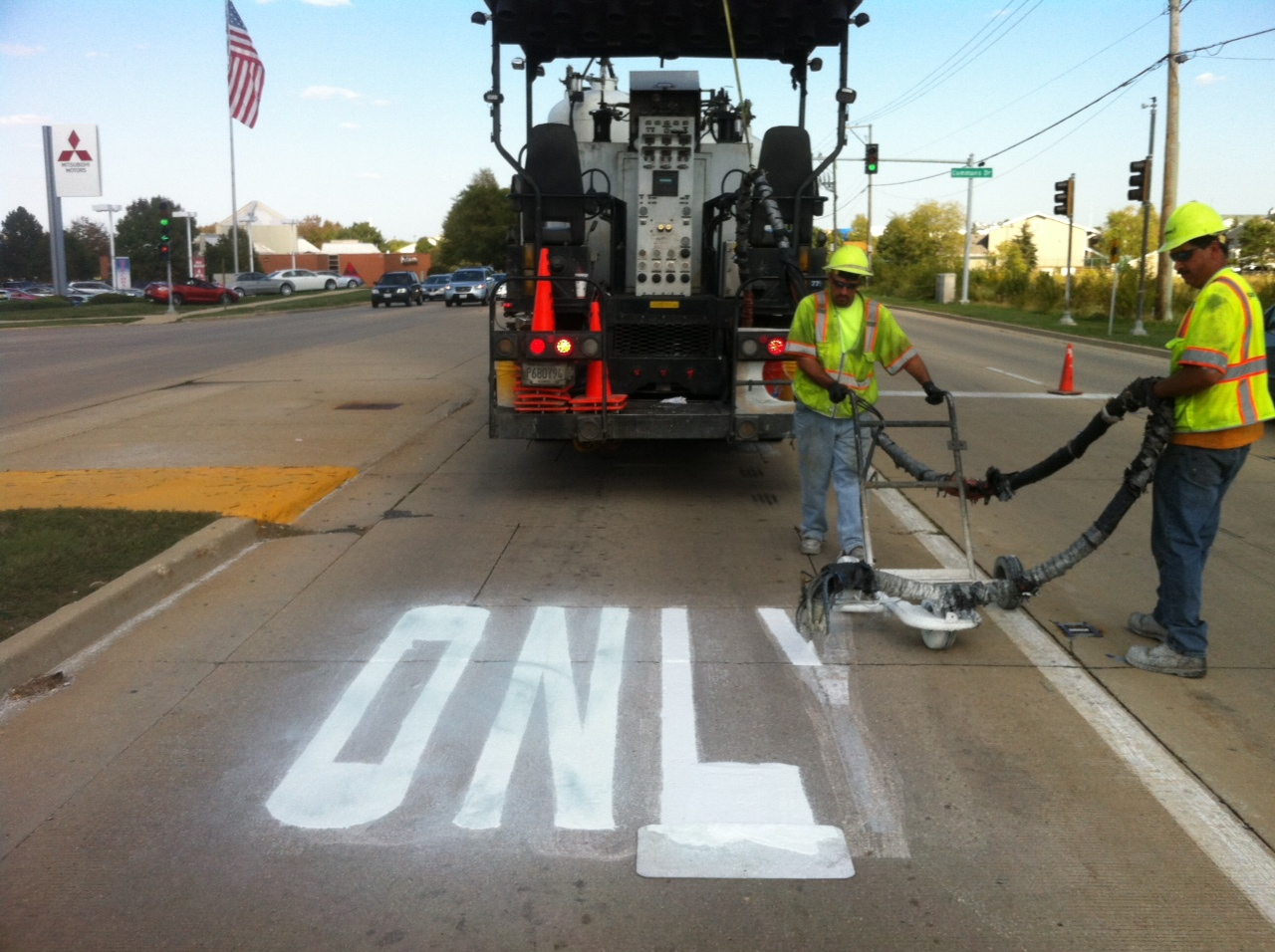 Image of RoadSafe employees painting a turn lane.