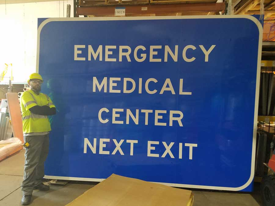 """Image of large sign that says """"Emergency Medical Center Next Exit""""."""