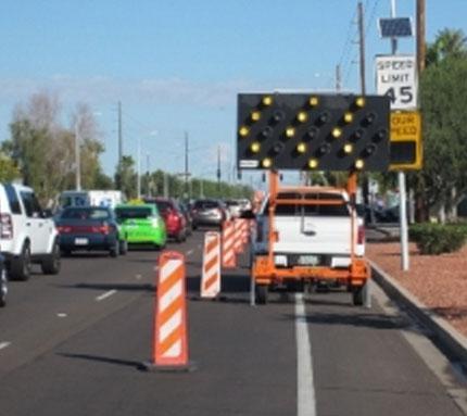 Image of barricades and sign indicating closed lane.